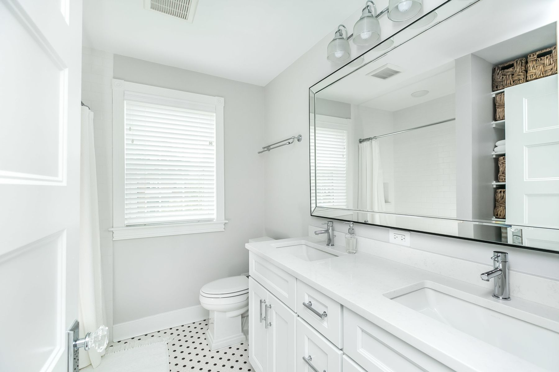 View of bathroom on and large mirror across shared sinks