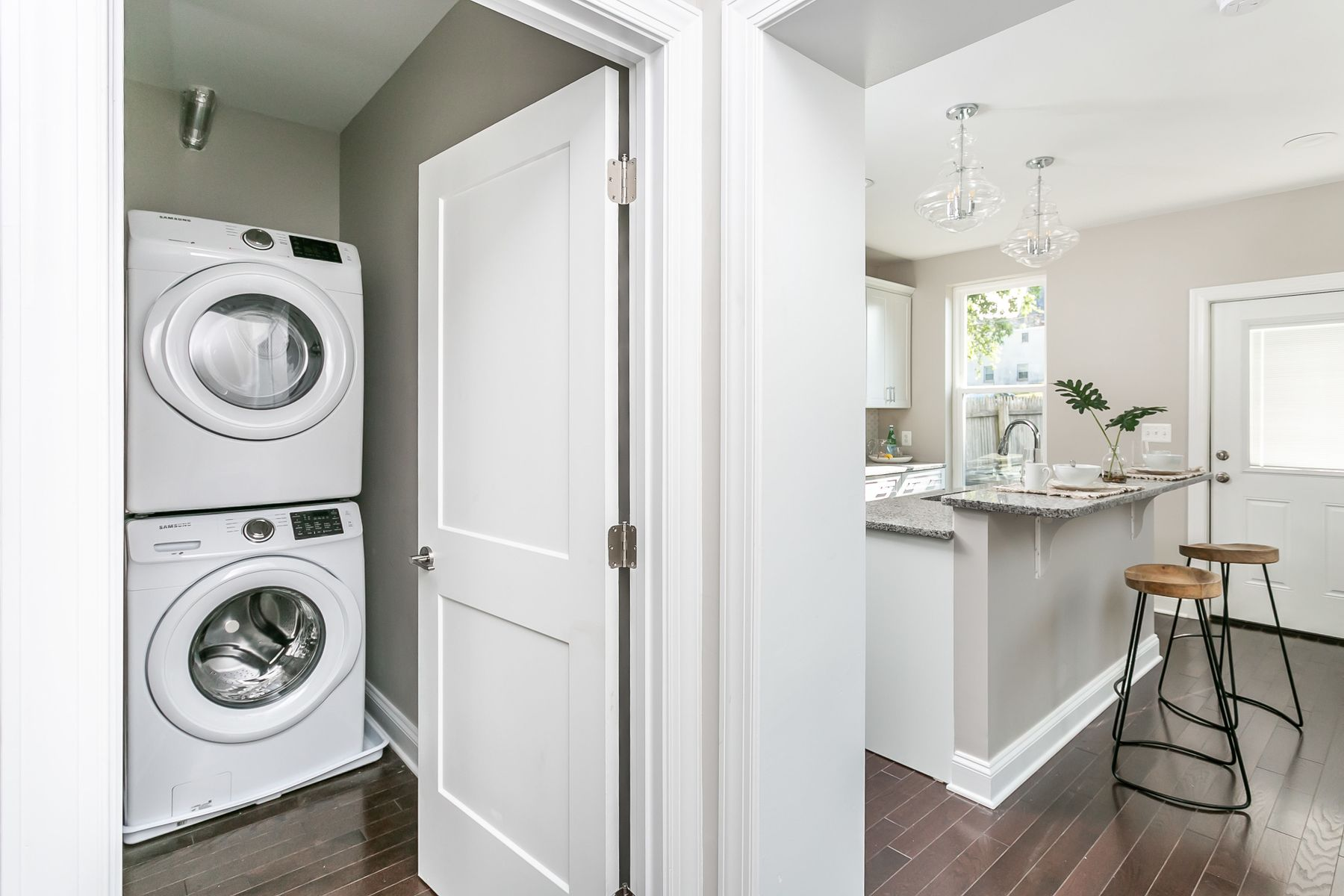 Laundry room with washer and dryer in entrance to brand new kitchen